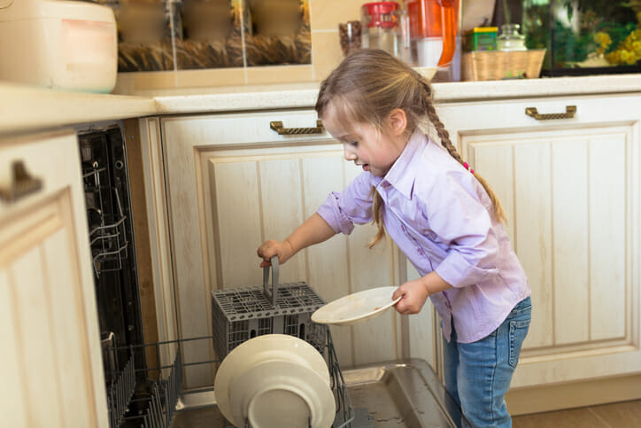 a young girl emptying the dishwasher